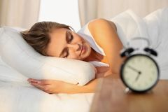 Beautiful young woman sleeping and smiling while lying in bed comfortably and blissfully on the background of alarm. Clock is going to ring. Sunbeam dawn on her Stock Photos