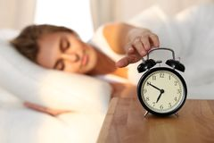 Beautiful young woman sleeping and smiling while lying in bed comfortably and blissfully on the background of alarm. Clock is going to ring. Sunbeam dawn on her Royalty Free Stock Photos