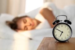 Beautiful young woman sleeping and smiling while lying in bed comfortably and blissfully on the background of alarm. Clock is going to ring. Sunbeam dawn on her Stock Photo