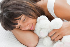 Beautiful young woman sleeping with a teddy bear Stock Photos