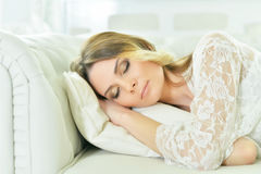 Beautiful young woman sleeping. On white couch with pillow Stock Images