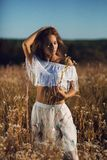 Beautiful young woman with slim body standing posing in the meadow on sunset royalty free stock image