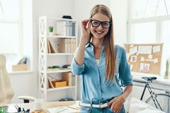 Beautiful young woman. In smart casual wear looking at camera and smiling while standing in the office royalty free stock images