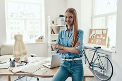 Beautiful young woman. In smart casual wear looking at camera and smiling while standing in the office stock images