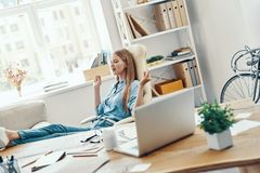 Beautiful young woman. In smart casual wear smiling and meditating while working in the office stock photo