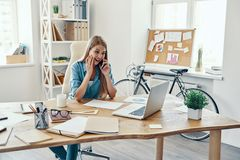 Beautiful young woman. In smart casual wear smiling and talking on the phone while sitting in the office stock photos