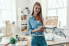 Beautiful young woman. In smart casual wear smiling and writing something down while standing in the office stock images