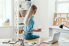 Beautiful young woman. In smart casual wear writing something down and using laptop while sitting in the office royalty free stock images