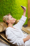 Beautiful young woman with smartphone at spa Stock Image