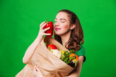 Beautiful young woman smelling fresh vegetables Royalty Free Stock Photo