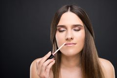 Beautiful young woman smelling the lipgloss applicator. On dark background Royalty Free Stock Images