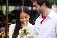 Beautiful young woman smelling rose with boyfriend smiling stock photos