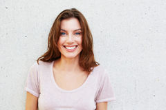 Beautiful young woman smiling against white wall Stock Photo