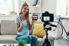 Beautiful young woman. Smiling and applying make-up pallet while making social media video at home stock photo