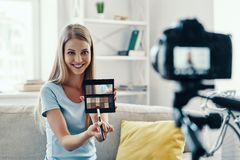 Beautiful young woman. Smiling and applying make-up pallet while making social media video at home stock photography