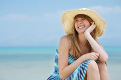 Beautiful young woman smiling on the beach. Beautiful young woman with sun hat sitting and smiling on the beach. Sea in background Royalty Free Stock Photos