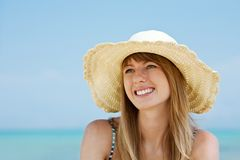 Beautiful young woman smiling on the beach. Beautiful young woman with sun hat sitting and smiling on the beach. Sea in background Royalty Free Stock Photo