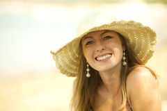 Beautiful young woman smiling on the beach. Beautiful young woman with the hat smiling on the beach. Perfect smile Royalty Free Stock Photography