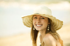 Beautiful young woman smiling on the beach. Beautiful young woman with the hat smiling on the beach. Perfect smile Royalty Free Stock Photo