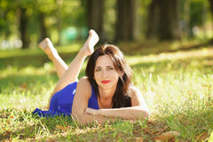 Beautiful young woman smiling in blue dress lying on the grass Royalty Free Stock Photography