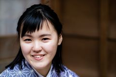 A beautiful young woman smiling into the camera wearing a kimono. A beautiful young girl looking into the camera while travelling in Japan Royalty Free Stock Photo