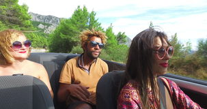Beautiful young woman smiling and enjoying driving her friends in convertible. Beautiful young woman dressed in boho style driving her friends in convertible stock footage