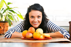 Beautiful young woman, smiling in front of the fruit plate. Pretty young woman, smiling in front of the fruit plate Royalty Free Stock Photos