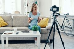 Beautiful young woman smiling. And gesturing while making social media video at home stock photo