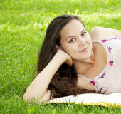 Beautiful young woman smiling on grass field. A very beautiful young woman lying down smiling in a field Stock Image