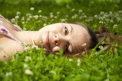 Beautiful young woman smiling on grass field. A very beautiful young woman lying down smiling in a field Royalty Free Stock Images