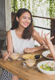 Beautiful young woman smiling while having lunch with friends Royalty Free Stock Photography