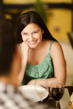 Beautiful young woman smiling at her partner. Beautiful young brunette woman smiling at her partner in a restaurant Stock Image