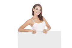 Beautiful young woman smiling while holding blank board Royalty Free Stock Photos