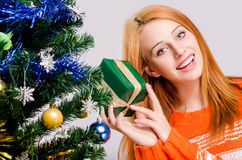 Beautiful young woman smiling holding a Christmas present. Royalty Free Stock Photography