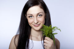 beautiful young woman smiling holding green dill Royalty Free Stock Photo