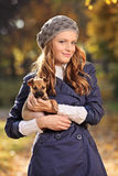 Beautiful young woman smiling and holding a puppy Royalty Free Stock Image