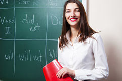 Beautiful young woman smiling near blackboard Stock Images