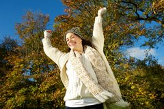 Beautiful young woman smiling  outdoors with arms outstretched Stock Photography
