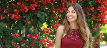 Beautiful young woman smiling outdoors in Spring / Summer time with red flowers on copy space background. Stock Photography