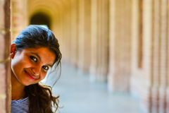 A beautiful young woman peeking from behind a wall royalty free stock photo