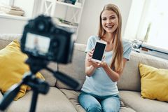 Beautiful young woman. Smiling and pointing copy space on her smart phone while making social media video at home royalty free stock photos