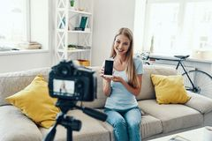 Beautiful young woman. Smiling and pointing copy space on her smart phone while making social media video at home royalty free stock photo