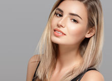 Beautiful young woman smiling posing with blond hair on gray background Stock Images
