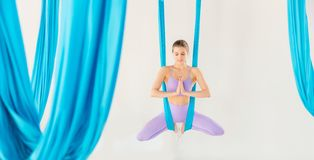Beautiful young woman smiling at practicing aero fly yoga in white studio on blue hammocks. Concept stretching. Beautiful young woman smiling at practicing royalty free stock images