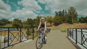 Beautiful young woman smiling while riding her bicycle on sunny summer day stock footage