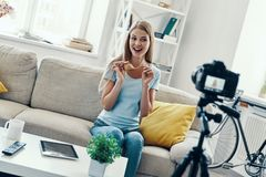 Beautiful young woman. Smiling and showing her hair tips while making social media video at home royalty free stock image