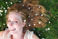 Beautiful young woman smiling with spring flowers in hair. Portrait of a beautiful young woman smiling with spring flowers in hair -  top view Royalty Free Stock Photography