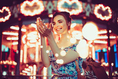 Beautiful young woman smiling and talking garlands of lights at city. Street Stock Images