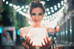 Beautiful young woman smiling and talking garlands of lights at city. Street Stock Photography