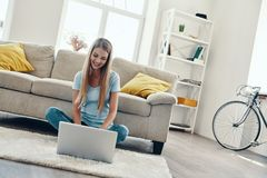 Beautiful young woman. Smiling and using laptop while resting at home royalty free stock photo